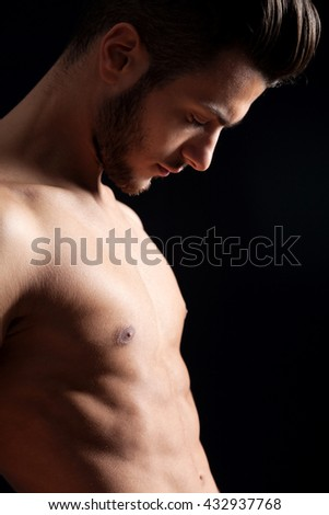 Attractive muscular man on black background - stock photo
