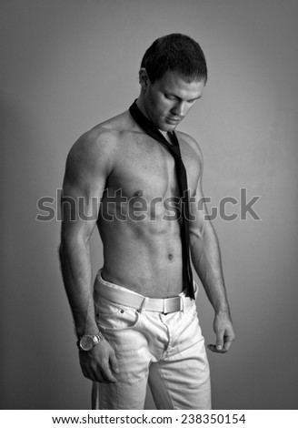 Attractive muscular man posing with tie. Black and white. - stock photo