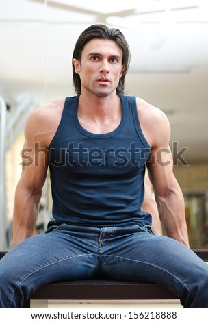 Attractive, muscular man sitting on desk indoors, wearing jeans and tank top - stock photo