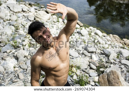 Attractive muscular shirtless young man in nature shielding eyes from sun with his hand - stock photo