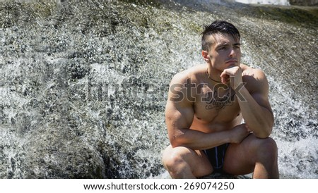 Attractive muscular shirtless young man under small waterfall on his knees - stock photo