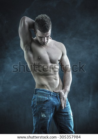 Attractive muscular young man shirtless with jeans isolated on black background - stock photo