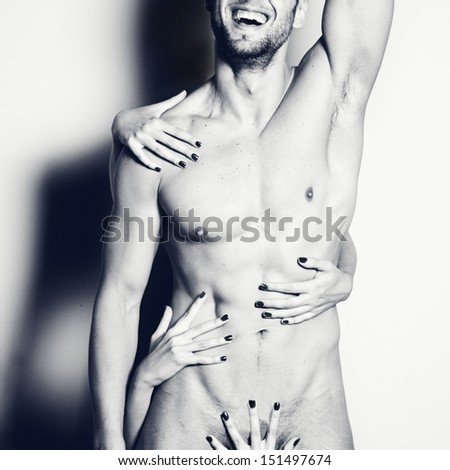 Attractive muscular young nude man, smiling with female hands,square - stock photo