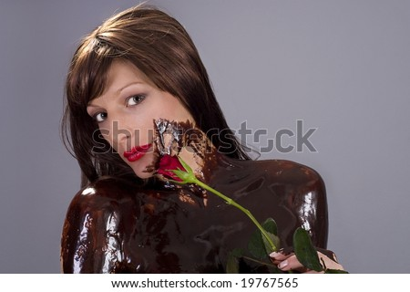 Attractive naked brunette girl covered in chocolate holding red rose