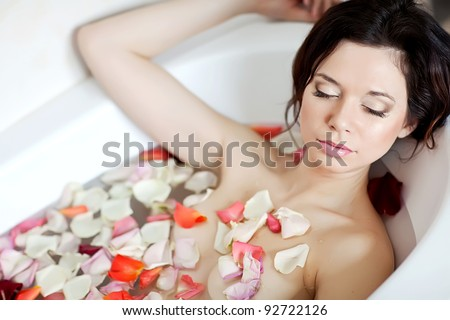 Attractive naked girl enjoys a bath with  and rose petals. Spa treatments for skin rejuvenation - stock photo