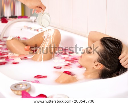 Attractive naked girl enjoys a bath with milk and rose petals.Spa treatment for nutrition and moisturizing skin renewal - stock photo