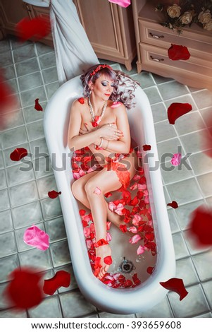 Attractive naked girl enjoys a bath with  rose petals. Spa treatments for skin rejuvenation. fashion interior photo of sexy beautiful woman with blond hair lying in petals in bathtub - stock photo