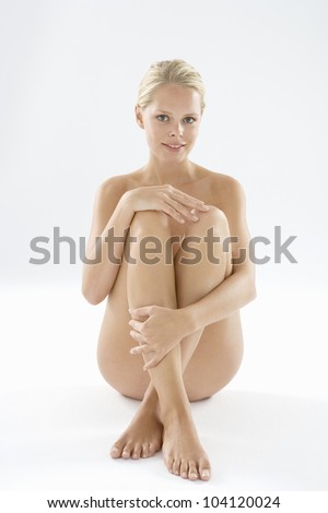 Attractive naked woman isolated on a white background, smiling at camera. - stock photo