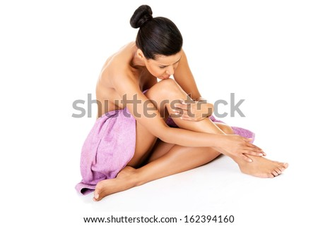 Attractive naked woman sitting covered with towel, touching legs. Isolated on white.  - stock photo