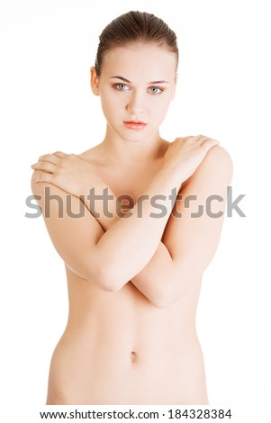 Attractive naked woman with crossed hands on her breasts. Front view. Isolated on white.