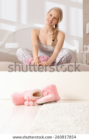 Attractive nordic woman sitting in tailor seat in bed, smiling, looking at camera. - stock photo