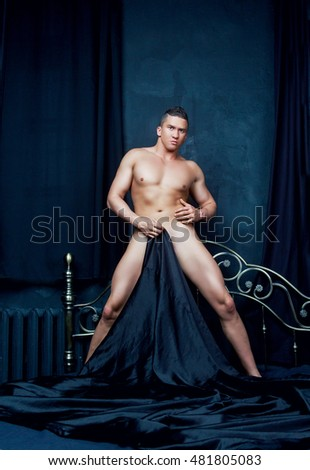 attractive nude man  in bed with black linen