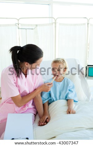 Attractive nurse examining a little female patient in a hospital