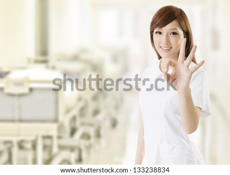 Attractive nurse give you an gesture of ok, closeup portrait at hospital. - stock photo