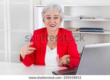 Attractive older smiling senior businesswoman sitting at desk wearing red jacket and explain something.
