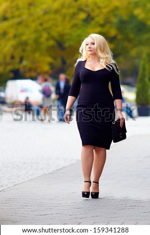 attractive overweight woman walking the city street - stock photo