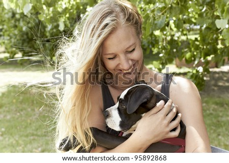 Attractive owner embraces her Pit Bull puppy - stock photo