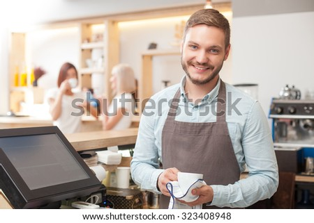 Attractive owner of coffee shop is holding a cup and drying it with towel. He is standing and looking at camera with joy. The man is smiling. Two women are talking and drinking coffee on background - stock photo