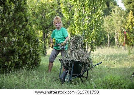 Attractive pensioner is working in the garden - stock photo