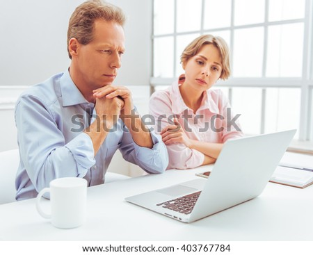 Attractive pensive business people are using a laptop and thinking while working in office