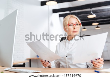 Attractive pensive mature businesswoman reading papers in office - stock photo