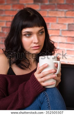 Attractive pensive young woman in sweater and jeans sitting and drinking tea over brick wall background