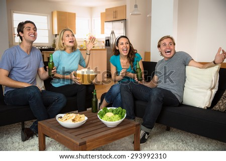Attractive people at home watching television movie scary film enthusiastic - stock photo