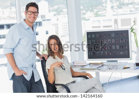 Attractive photo editors posing in their office next to a computer - stock photo