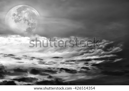 Attractive photo of a beautiful sky with clouds, bright full moon would make a great background. Beauty of nature use as background. Outdoors. Black and white picture style. - stock photo