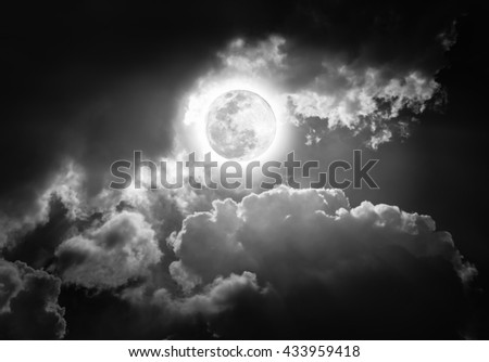 Attractive photo of a nighttime sky with clouds, bright full moon would make a great background. Beauty of nature in black and white. The moon taken with my own camera, no NASA images used. - stock photo