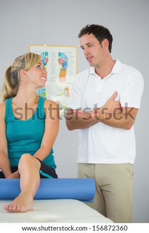 Attractive physiotherapist and patient looking at each other in bright office - stock photo