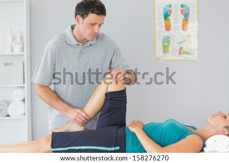 Attractive physiotherapist controlling knee of a patient in bright office - stock photo