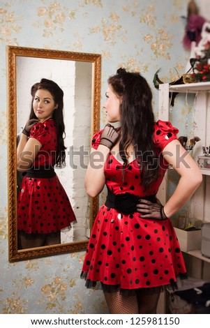 Attractive pin-up girl in front of the mirror - stock photo