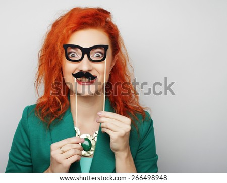 Attractive playful young woman holding mustache and glasses on a stick. Ready for party.