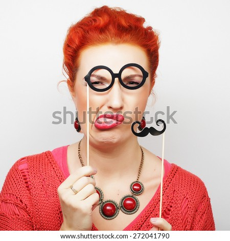 Attractive playful young woman holding mustache and glasses on a stick. Ready for party. - stock photo