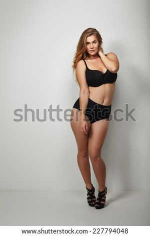 Attractive plus size young lady in bikini. Full length portrait of voluptuous young woman posing sensually on grey background - stock photo