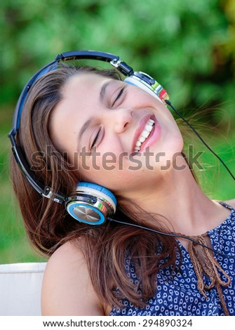 Attractive portrait of pretty girl listening to music - stock photo