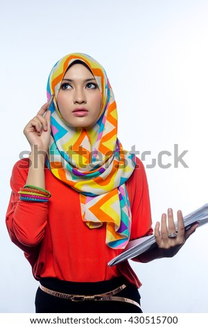 Attractive portrait of young muslim woman holding books, while thinking