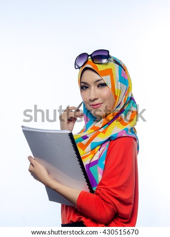 Attractive portrait of young muslim woman holding books, while thinking and smiling