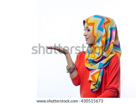 Attractive portrait of young muslim woman looking at her palm