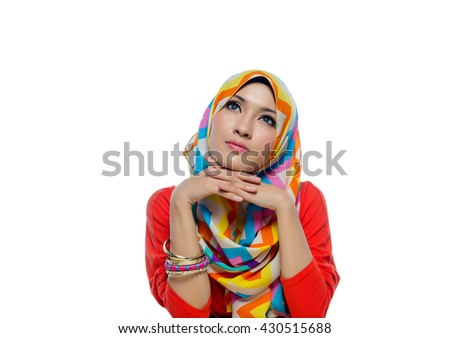 Attractive portrait of young muslim woman sitting while thinking and smiles