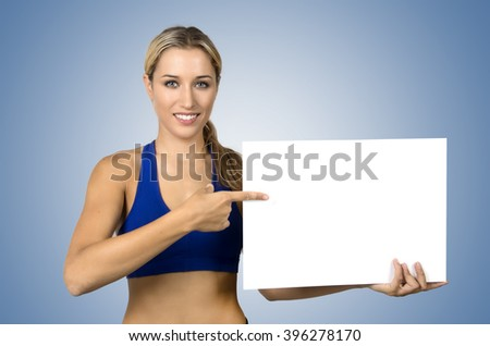 Attractive positive young sportswoman holding blank board and pointing on it