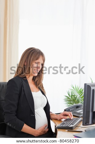 Attractive pregnant female working with a computer at the office - stock photo