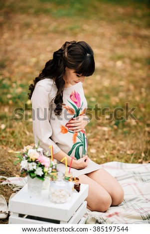 Attractive pregnant woman  is sitting with her hand on belly on checkered blanket in the autumn park on picnic. - stock photo