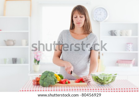 Attractive pregnant woman posing while cooking vegetables in a kitchen - stock photo