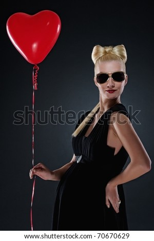 Attractive pregnant woman with a red balloon - stock photo