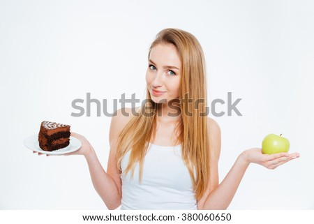 Attractive pretty young woman standing and holding healthy and unhealthy food over white background