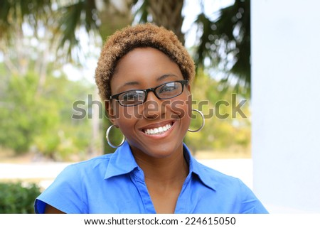 Attractive Professional African American Business Woman Person Black Hair Blue Shirt Wearing Glasses and Smiling - stock photo