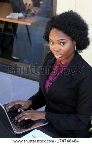 Attractive Professional African American Business Woman Wearing a Black Suit Looking Serious - stock photo