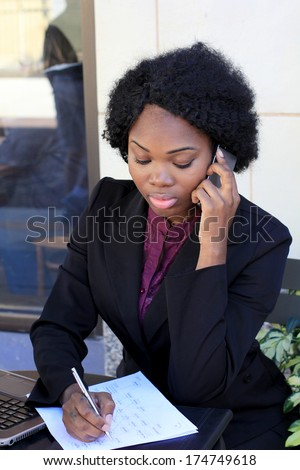Attractive Professional African American Business Woman Wearing a Black Suit Working On Computer and Writing and Talking On Phone - stock photo